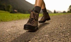 A woman wearing hiking boots walking down a trail