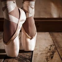 Wearing ballet slippers and on her toes