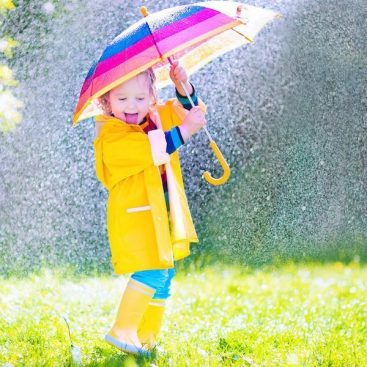 Funny toddler with umbrella playing in the rain, pink and purple