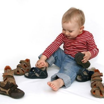 baby putting on shoes by himself