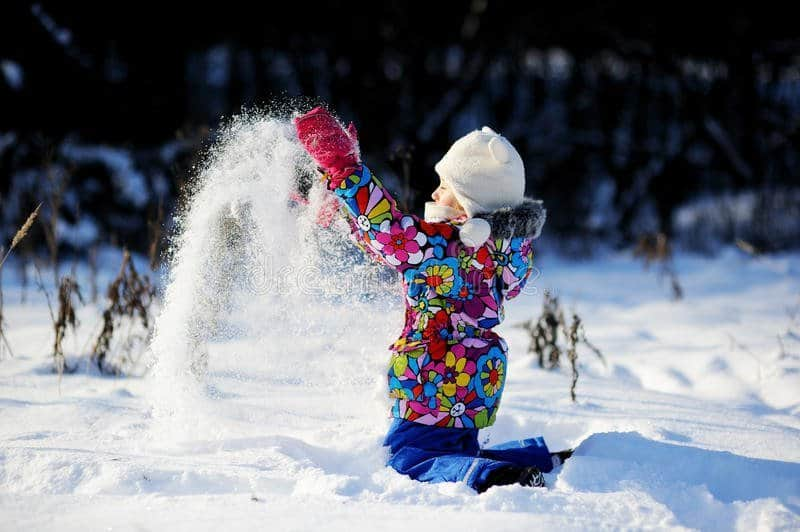 toddler-girl-colorful-snowsuit-plays-snow